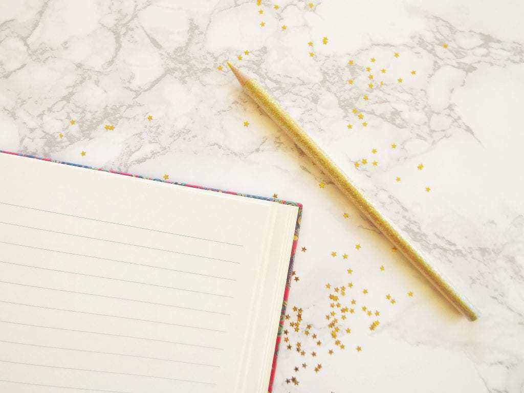 Golden pencil and notebook