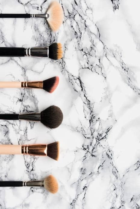 makeup brushes on marble background
